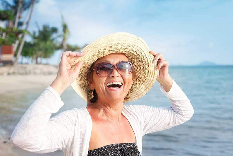 a happy, smiling woman on the beach