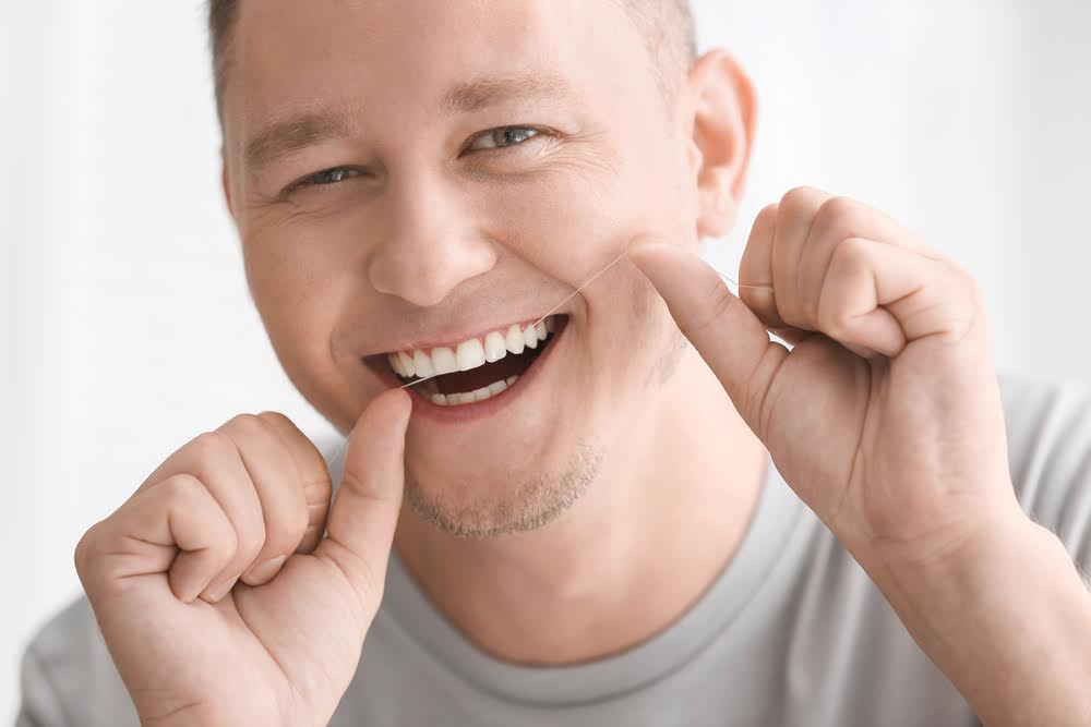 A man wearing a gray shirt flossing his teeth to properly care for his dental crown
