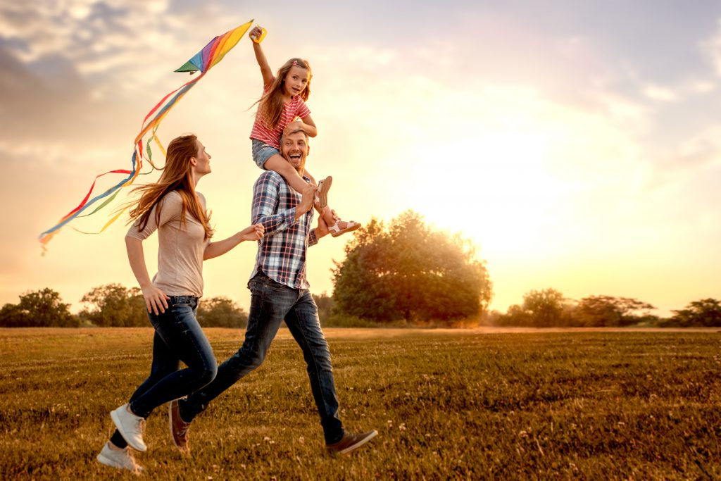 A family flying a kite, laughing